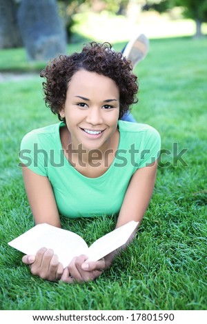 A pretty African American woman reading a book at the park - stock photo