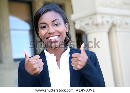 A pretty african american woman student at college with thumbs up - stock photo