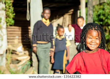 a pretty african girl with braided hair and a bright red shirt smiling confidently with her siblings in the backround watching over her - stock photo