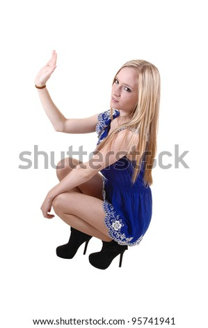 A pretty and slim young woman crouching in her blue short dress and  long blond long hair in black boots for white background in the studio. - stock photo
