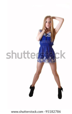 A pretty and slim young woman standing in her blue short dress and  long blond long hair in black boots for white background in the studio. - stock photo