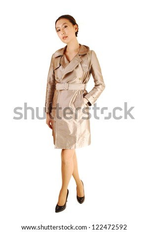 A pretty and young Asian woman standing in a beige coat for white background, looking into the camera.