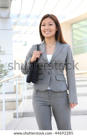 A pretty asian business woman at office building - stock photo