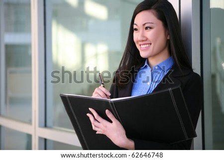 A pretty asian business woman with notebook at office building - stock photo