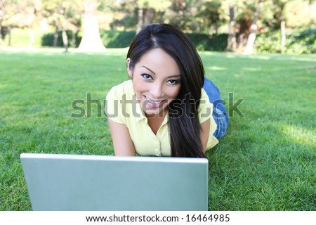 A pretty asian girl working on laptop computer on grass in the park