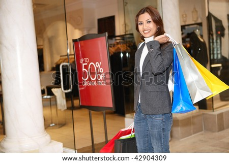 A pretty asian woman holding sale bags shopping in the mall - stock photo
