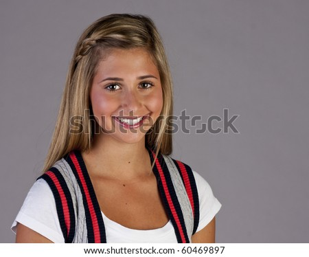 a pretty blond young teen girl standing with a cute smile.