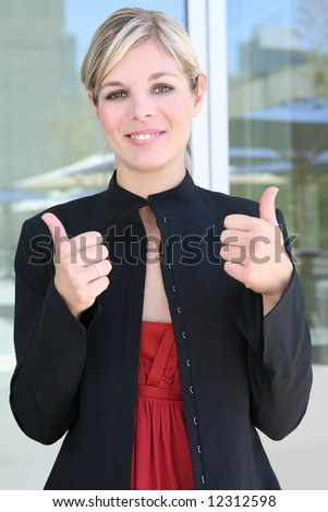A pretty blonde business woman with her thumbs up