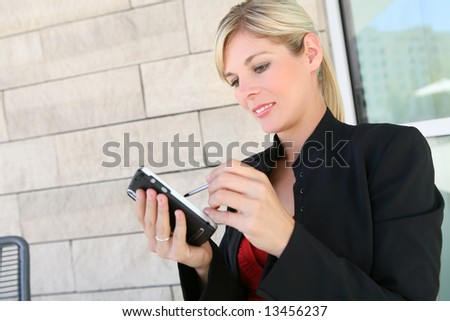 A pretty blonde business woman working on pda at office building - stock photo