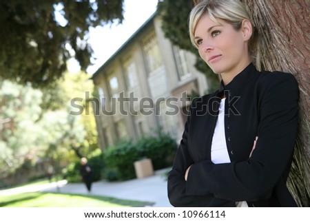 A pretty blonde student at her college leaning on tree - stock photo