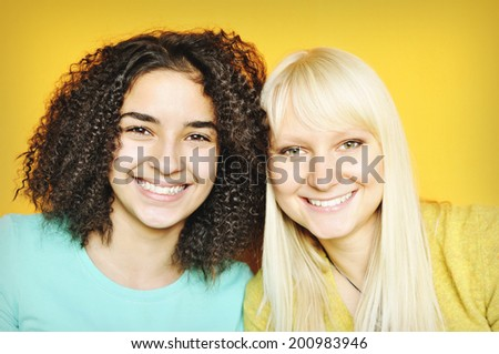 A pretty brunette with a pretty blonde girl isolated on yellow background.  - stock photo
