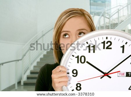 A pretty business woman hiding behind a clock - stock photo