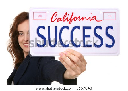 A pretty business woman holding a success license plate - stock photo