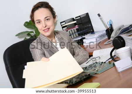 A pretty business woman in the office handing folders to boss - stock photo