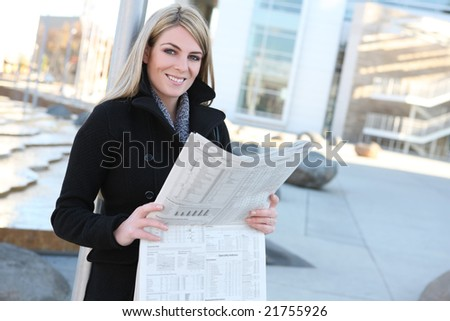 A pretty business woman reading the newspaper outside her company