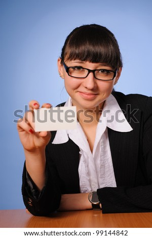 A pretty business woman sitting at table and hold business card - stock photo