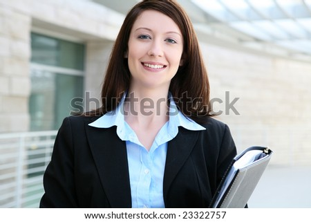 A pretty business woman walking to work at the office - stock photo