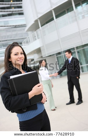 A pretty business woman with team handshake in background