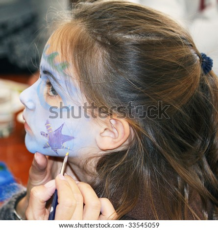 a pretty caucasian girl getting her face painted - stock photo