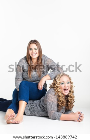 a pretty caucasian girl sitting on top of her laughing friend with her arm resting on her curly head with both girls wearing matching jerseys - stock photo