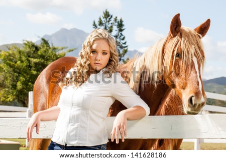 a pretty caucasian girl with blond curly hair leaning against a white picket fence with her mahogany colored horse standing with perk ears behind her - stock photo