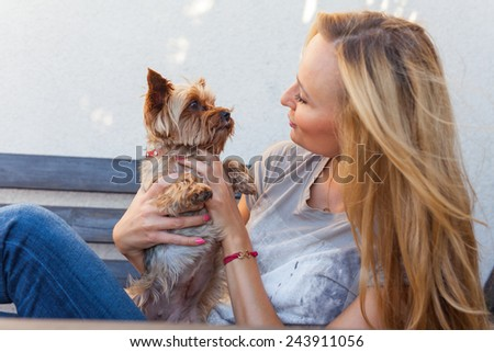 A pretty caucasian woman at home sitting on the porch and playing with a dog. Outdoor photo.