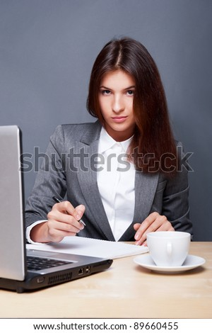 A pretty concentrated woman working with her laptop and papers. Sitting at her office