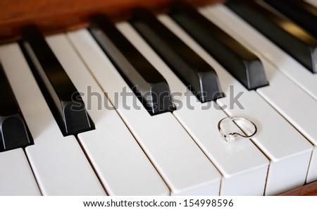 A pretty diamond ring on a piano - stock photo