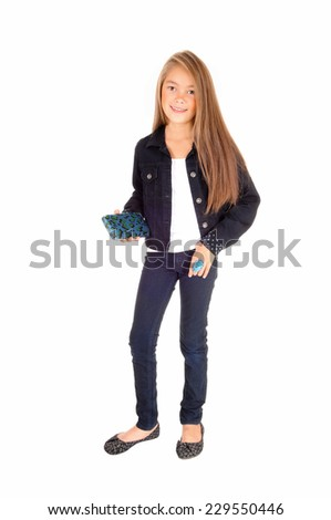 A pretty eight year old girl standing isolated for white background in jeans and a jean jacket, holding her purse.  - stock photo