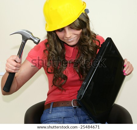 A pretty girl fixes her laptop with a large hammer