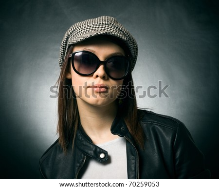 A pretty girl in a cap and sunglasses on a dark background. - stock photo