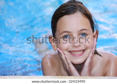 a pretty girl with blue eyes relaxing in a swimming pool smiling and looking at camera - stock photo