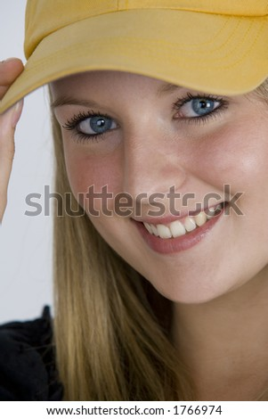 A pretty girl with bright blue eyes and blonde hair and wearing a baseball cap. - stock photo