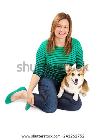 A pretty lady wearing a green and blue striped shirt holding a Welsh Corgi dog - stock photo
