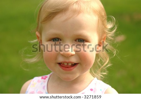 A pretty little girl (almost 3 years old) outside in a flowered dress - stock photo