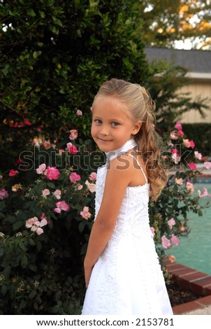 A pretty little girl dressed in a long white dress.  She has blonde hair and blue eyes and is standing by a bed of pink roses. Her Hair has long flowing curls. - stock photo