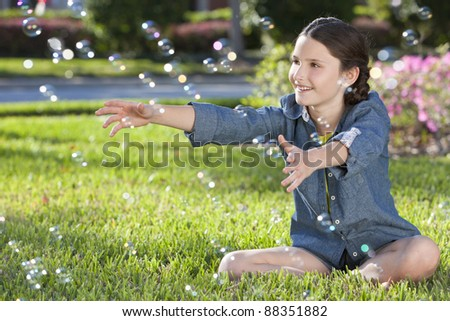 A pretty little girl sitting in sunshine on grass on a summer day playing and blowing bubbles - stock photo