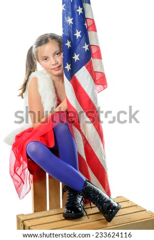 a pretty little girl sitting on a box with a american flag on the white background - stock photo