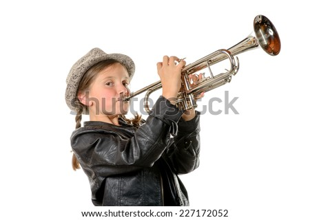 a pretty little girl with a black jacket and hat plays the trumpet - stock photo