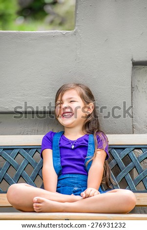 A pretty little girl,with long dark hair, and purple shirt, sits on an outside bench in the garden with her legs folded, while laughing with joy. - stock photo