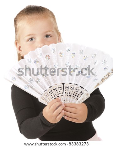 A pretty little preschooler peering over the fancy, sparkly white hand-fan she'd holding. - stock photo