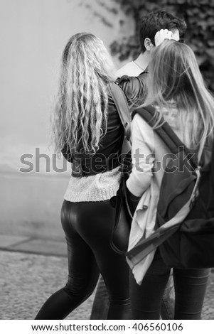 A pretty long blond hair girl in her tight black leather leggings interacting with her school mates - back view - black and white photograph - stock photo