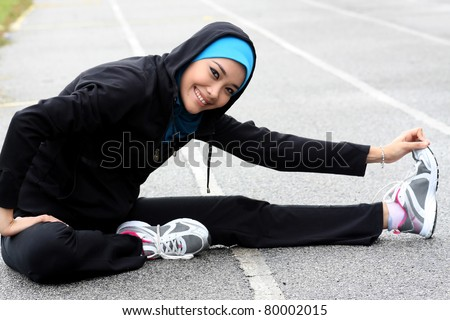 A pretty muslim woman athlete stretching her body at stadium track - stock photo