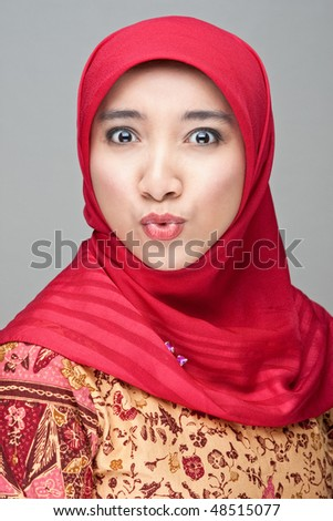 A pretty Muslim woman wearing a traditional Batik  looking impressed/surprised. - stock photo
