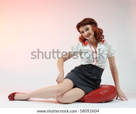A pretty pin up girl sitting on a red cushion. - stock photo