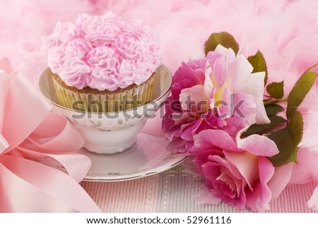 A pretty pink cupcake in a teacup surrounded by pink boa, bow, and pink roses, horizontal with copy space - stock photo