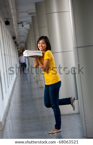 A pretty playful college student wearing yellow t-shirt balances on one leg with her books held near face.  Twenties female Asian Thai model of Chinese descent looking at camera
