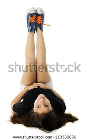 A pretty preteen looking back over her head at the viewer as she lays in her back, legs straight up in the air to show off her blue sneakers with bright orange laces.  On a white background. - stock photo