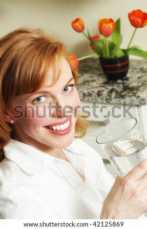 a pretty redhead takes a drink of cool clean water