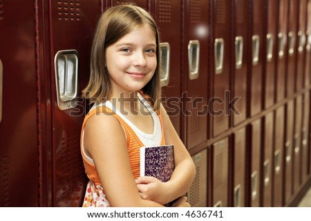 A pretty school girl leaning against her locker. - stock photo